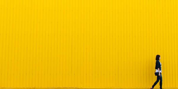 Woman walking passed a yellow wall NetSuite Training